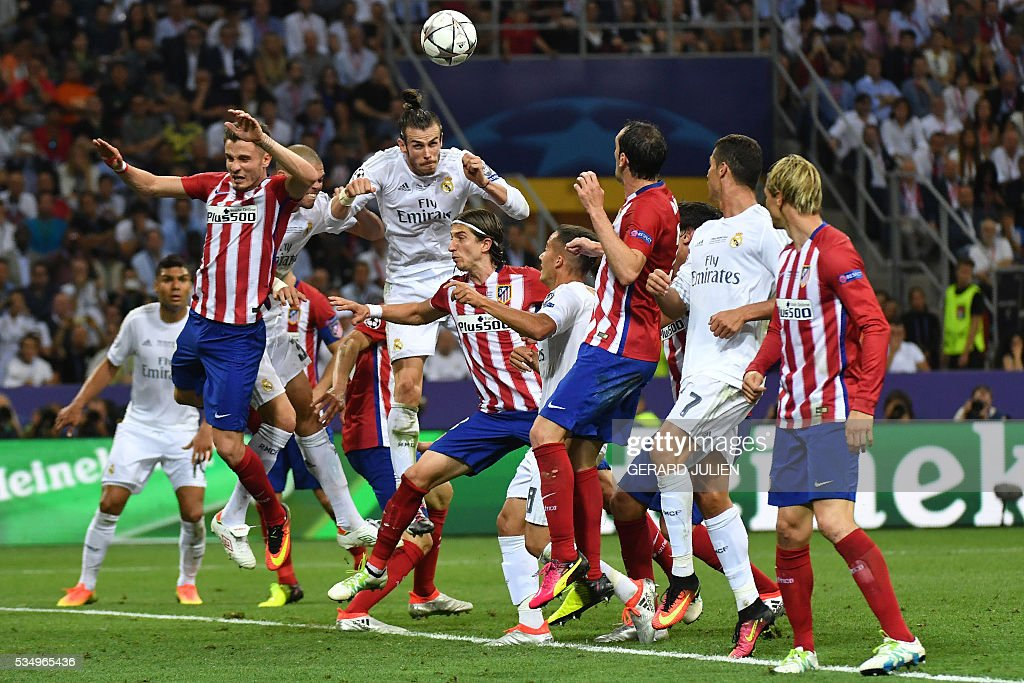 Real Madrid's Welsh forward Gareth Bale (C) jumps for the ball during the UEFA Champions League final football match between Real Madrid and Atletico Madrid at San Siro Stadium in Milan, on May 28, 2016. / AFP / GERARD