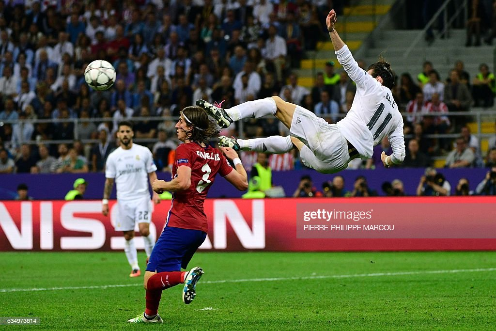 Real Madrid's Welsh forward Gareth Bale (L) jumps to kick the ball next to Atletico Madrid's Brazilian defender Filipe Luis during the UEFA Champions League final football match between Real Madrid and Atletico Madrid at San Siro Stadium in Milan, on May 28, 2016. / AFP / PIERRE