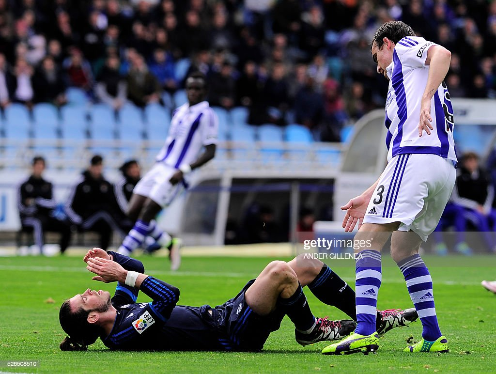 Real Madrid's Welsh forward Gareth Bale lies on the ground next to Real Sociedad's defender Mikel Gonzalez during the Spanish league football match...