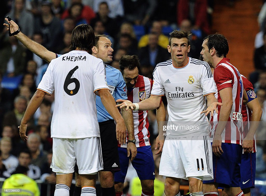 Real Madrid's Welsh forward Gareth Bale (R) reacts during the Spanish league football match Real Madrid CF vs Club Atletico de Madrid at the Santiago Bernabeu stadium in Madrid on September 28, 2013. Atletico won 1-0.