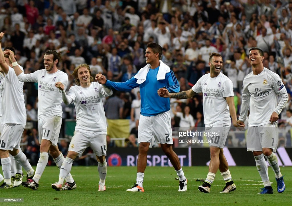 Real Madrid's Welsh forward Gareth Bale, Real Madrid's Croatian midfielder Luka Modric, Real Madrid's French defender Raphael Varane, Real Madrid's forward Jese Rodriguez and Real Madrid's Portuguese forward Cristiano Ronaldo celebrate their victory at the end of the UEFA Champions League semi-final second leg football match Real Madrid CF vs Manchester City FC at the Santiago Bernabeu stadium in Madrid, on May 4, 2016. Real Madrid won 1-0. / AFP PHOTO / GERARD JULIEN / The erroneous mention[s] appearing in the metadata of this photo by GERARD JULIEN has been modified in AFP systems in the following manner: [Real Madrid's French defender Raphael Varane] instead of [Real Madrid's Costa Rican goalkeeper Keylor Navas]. Please immediately remove the erroneous mention[s] from all your online services and delete it (them) from your servers. If you have been authorized by AFP to distribute it (them) to third parties, please ensure that the same actions are carried out by them. Failure to promptly comply with these instructions will entail liability on your part for any continued or post notification usage. Therefore we thank you very much for all your attention and prompt action. We are sorry for the inconvenience this notification may cause and remain at your disposal for any further information you may require.