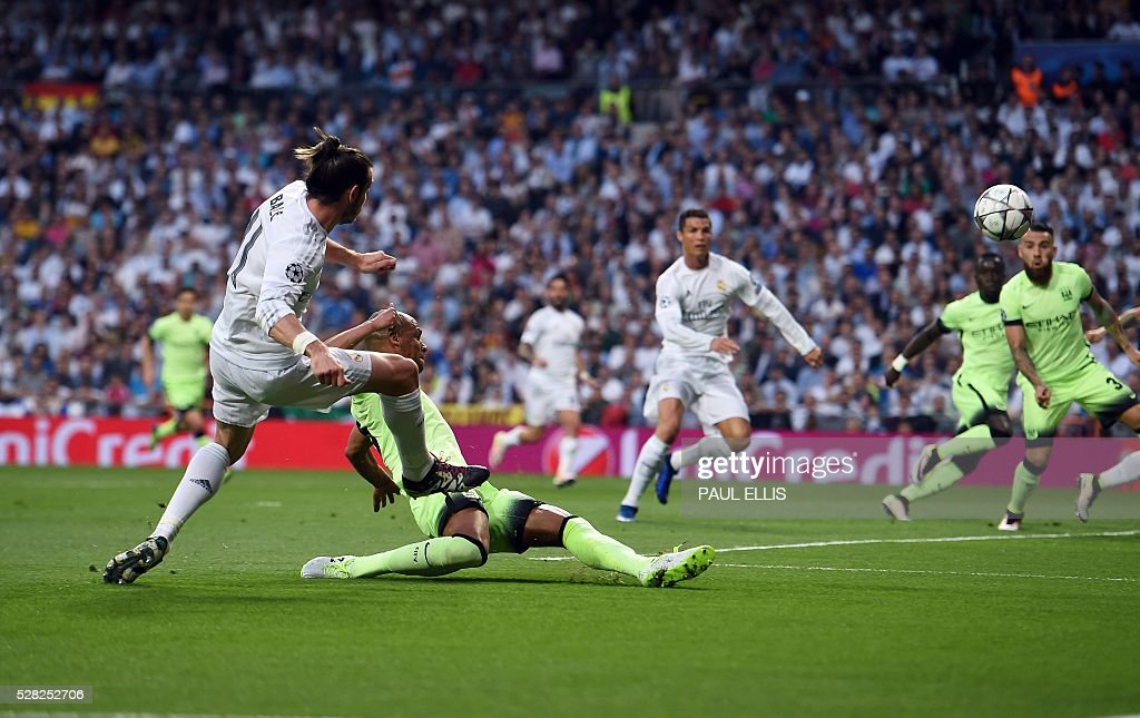 Real Madrid's Welsh forward Gareth Bale (L) scores past Manchester City's Brazilian midfielder Fernandinho during the UEFA Champions League semi-final second leg football match Real Madrid CF vs Manchester City FC at the Santiago Bernabeu stadium in Madrid, on May 4, 2016. / AFP / PAUL