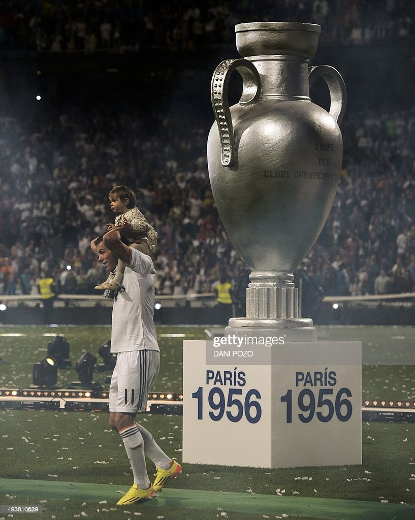 Real Madrid's Welsh forward Gareth Bale stands next to a sculpture of the Champions League trophy while Real Madrid's players celebrate their Champions League title at the Santiago Bernabeu stadium in Madrid on May 25, 2014, a day after beating Atletico Madrid 4-1 at the Luz stadium in Lisbon, Portugal. AFP PHOTO / DANI POZO