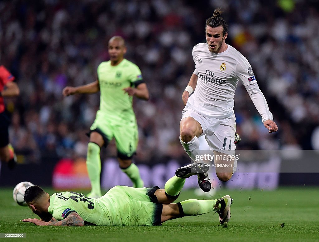 Real Madrid's Welsh forward Gareth Bale vies with Manchester City's Argentinian defender Nicolas Otamendi (bottom) during the UEFA Champions League semi-final second leg football match Real Madrid CF vs Manchester City FC at the Santiago Bernabeu stadium in Madrid, on May 4, 2016. / AFP / JAVIER