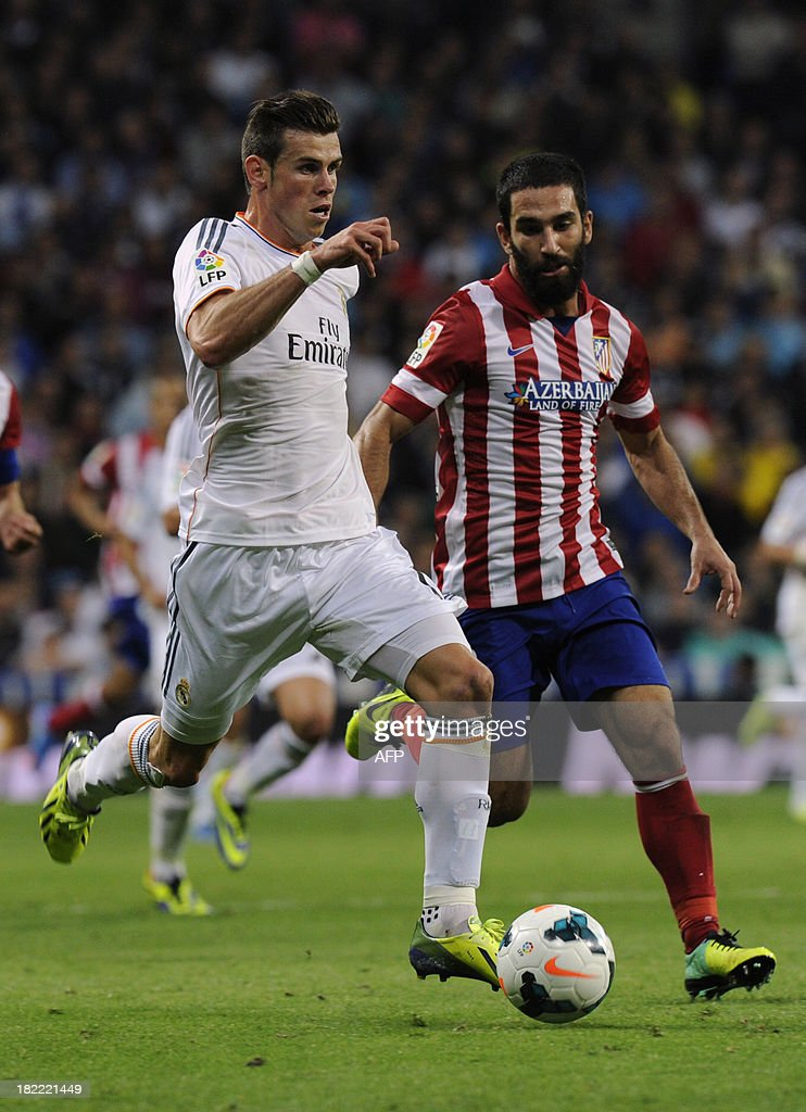 Real Madrid's Welsh striker Gareth Bale (L) vies with Atletico Madrid's Turkish midfielder Arda Turan during the Spanish league football match Real Madrid CF vs Club Atletico de Madrid at the Santiago Bernabeu stadium in Madrid on September 28, 2013. Atletico won 1-0.