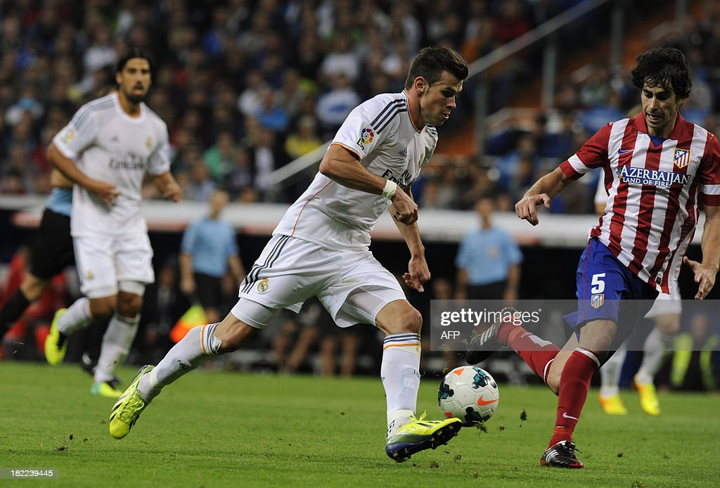 Real Madrid's Welsh striker Gareth Bale vies with Atletico Madrid's Portuguese midfielder Tiago Mendes during the Spanish league football match Real Madrid CF vs Club Atletico de Madrid at the Santiago Bernabeu stadium in Madrid on September 28, 2013. Atletico won 1-0.