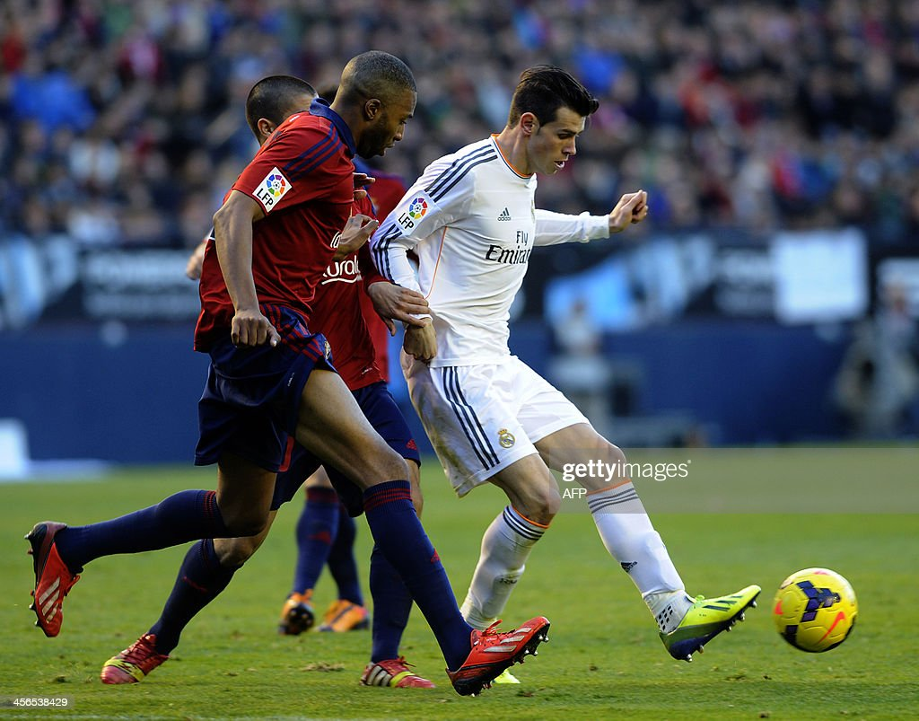 Real Madrid's Welsh striker Gareth Bale (R) vies with Osasuna's Loties (L) during the Spanish league football match Osasuna vs Real Madrid at the Reyno de Navarra in Pamplona on December 14, 2013.