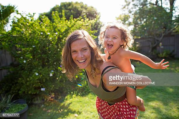 Real mother with child flying on back in garden