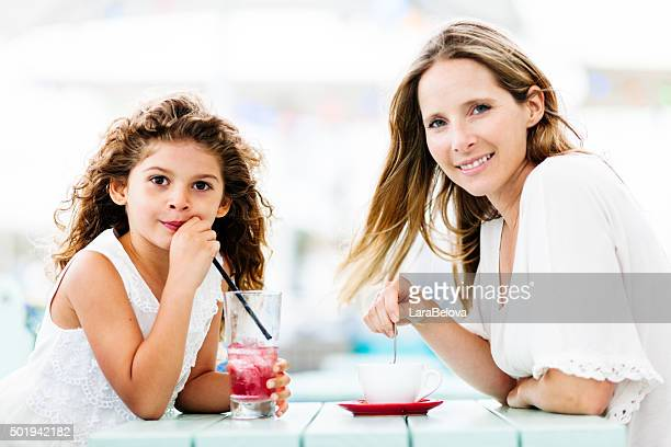 Real mother with daughter in sidewalk cafe