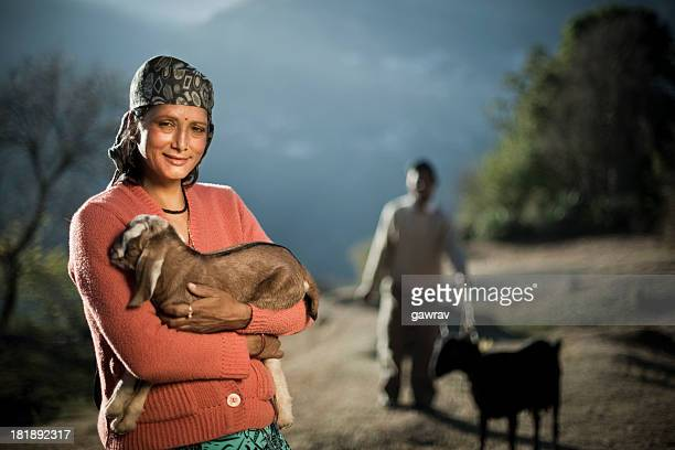 Real people from rural India: Happy woman holding goat kid