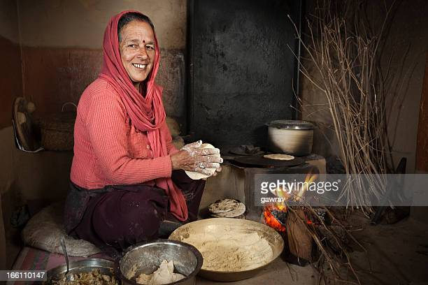 Real people from rural India: Senior woman cooking traditional food.