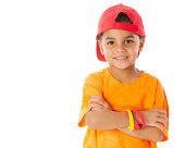 A head and shoulders image of a smiling mixed race (Caucasian and African American) little boy wearing bright clothes and a baseball cap.