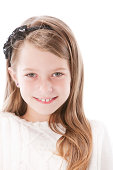 A head and shoulders image of a smiling caucasian 7-8 year old little girl with a hair bow and pierced ears.