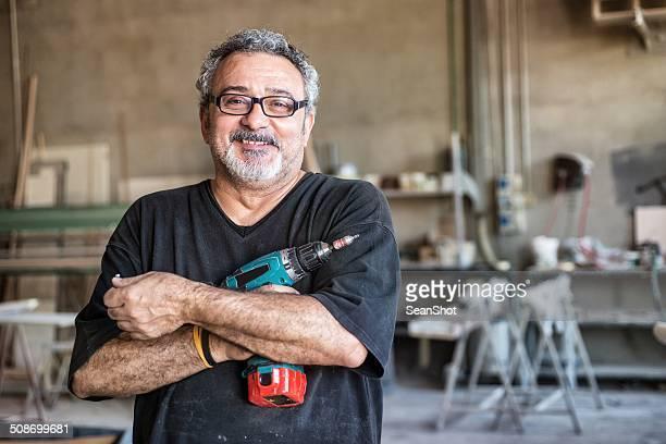 Echte Menschen-Arbeiter mit einem Bohrer