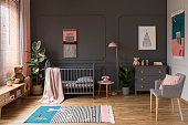 Real photo of a grey crib standing next to a pink stool, a lamp and cupboard in grey baby room interior also with armchair, rug and posters