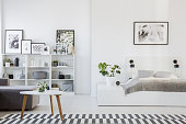Real photo of a platform bed standing next to a sofa and a table in a one room flat interior with shelves with ornaments and posters in the background