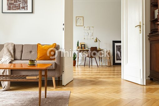 Real photo of a retro living room interior and view of a home office. View through a door : Stock Photo