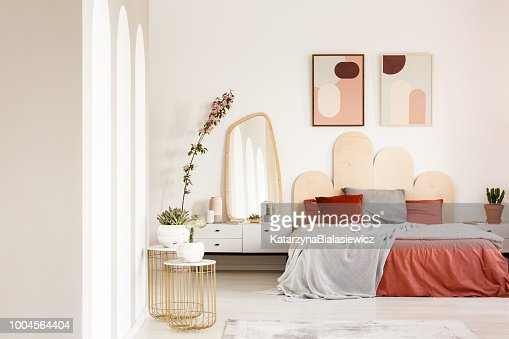 Real photo of a wide bed standing between a shelf with a plant and  a shelf with a mirror in a rusty bedroom interior with two posters on a wall and two gold, small tables with plants : Stock Photo