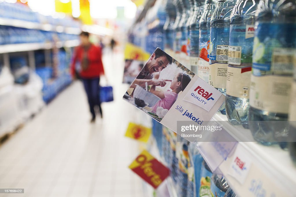 A Real quality product sign hangs from an aisle beside water bottles inside a Real supermarket in Wroclaw, Poland, on Wednesday, Dec. 5, 2012. Metro AG, Germany's biggest retailer, agreed to sell its Real grocery stores in eastern Europe to Groupe Auchan SA of France for 1.1 billion euros ($1.4 billion) in Chief Executive Officer Olaf Koch's first big deal since taking the helm. Photographer: Bartek Sadowski/Bloomberg via Getty Images