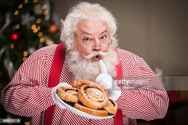 Real Santa hält Teller Zimtbrötchen