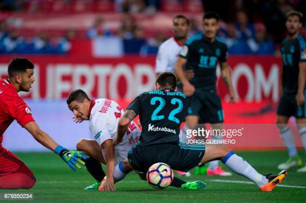 Real Sociedad's Argentinian goalkeeper Geronimo Rulli and defender Raul Navas vie with Sevilla's French Tunisian forward Wissam Ben Yedder during the...