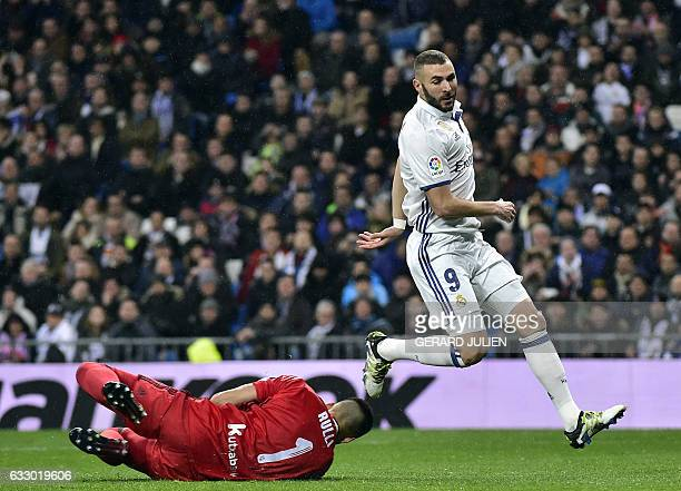 Real Sociedad's Argentinian goalkeeper Geronimo Rulli secures a ball beside Real Madrid's French forward Karim Benzema during the Spanish league...