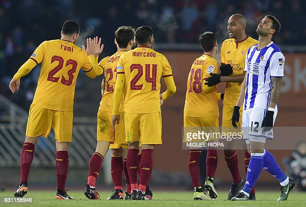 Real Sociedad's Brazilian forward Willian Jose gestures as Sevilla players celebrate their 4th goal during the Spanish league football match Real...