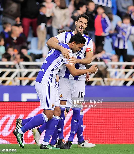 Real Sociedad's Brazilian forward Willian Jose is congratulated by teammate midfielder Xabier Prieto after scoring his team's first goal during the...