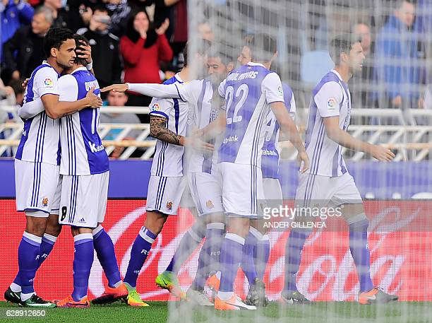 Real Sociedad's Brazilian forward Willian Jose is congratulated by teammate forward Mikel Oyarzabal after scoring his team's first goal during the...