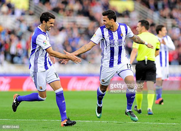 Real Sociedad's Brazilian forward Willian Jose is congratulated by teammate midfielder Xabier Prieto after scoring his team's second goal during the...