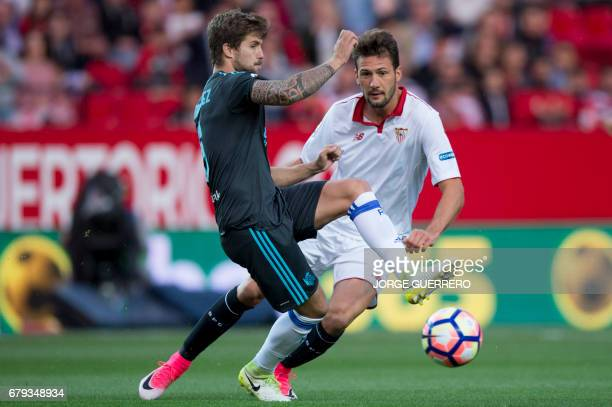 Real Sociedad's defender Inigo Martinez vies with Sevilla's Argentinian midfielder Franco Vazquez during the Spanish league football match Sevilla FC...