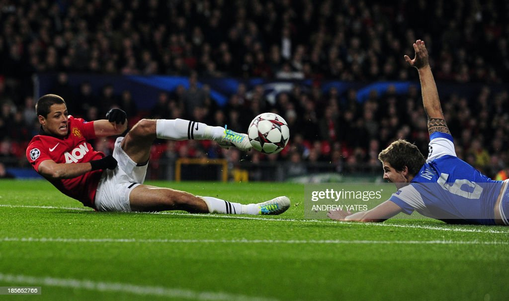 Real Sociedad's defender Inigo Martinez (R) watches as Manchester United's Mexican striker Javier Hernandez miskicks a shot during the UEFA Champions League football match between Manchester United and Real Sociedad at Old Trafford in Manchester, north west England on October 23, 2013.