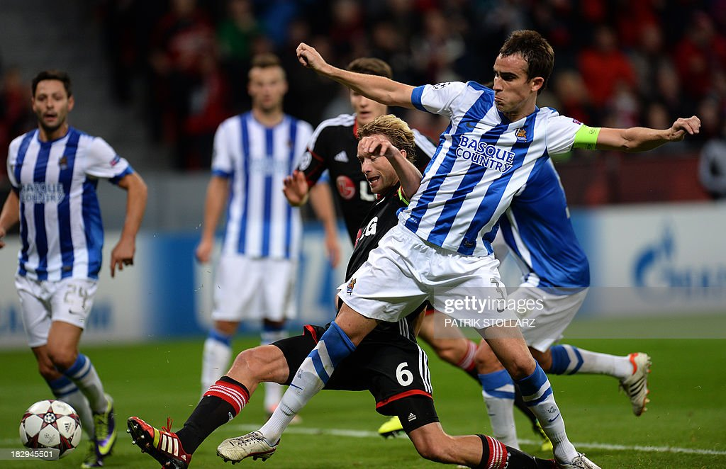 Real Sociedad's defender Mikel Gonzalez and Leverkusen's midfielder Simon Rolfes vie for the ball during the UEFA Champions League group A football...