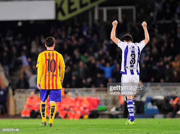 Real Sociedad's defender Mikel Gonzalez celebrates their victory past Barcelona's Argentinian forward Lionel Messi at the end of the Spanish league...