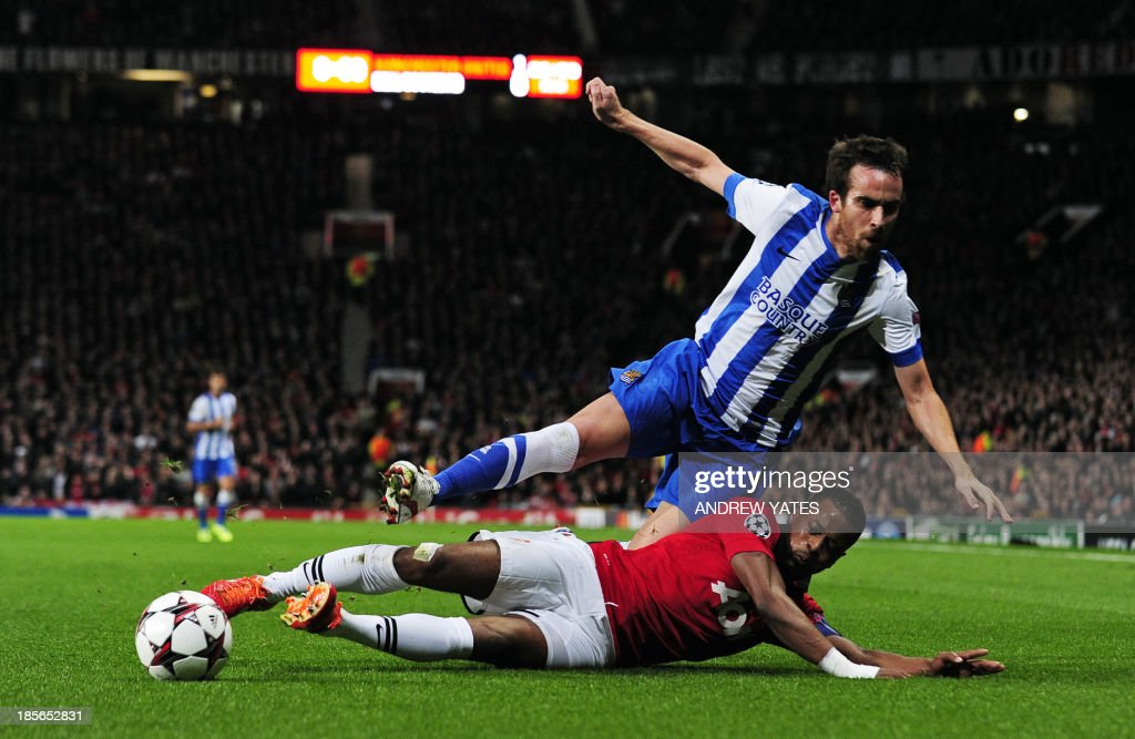 Real Sociedad's defender Mikel Gonzalez (up) vies with Manchester United's French defender Patrice Evra during the UEFA Champions League football match between Manchester United and Real Sociedad at Old Trafford in Manchester, north west England on October 23, 2013.