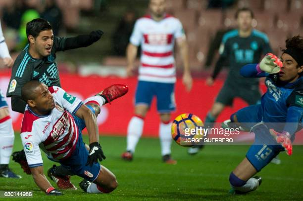 Real Sociedad's Mexican forward Carlos Vela vies with Granada's Brazilian defender Antunes da Silva and Mexican goalkeeper Guillermo Ochoa during the...