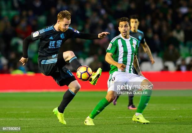 Real Sociedad's midfielder David Zurutuza controls the ball past Betis' Brazilian midfielder Petros during the Spanish league football match Real...