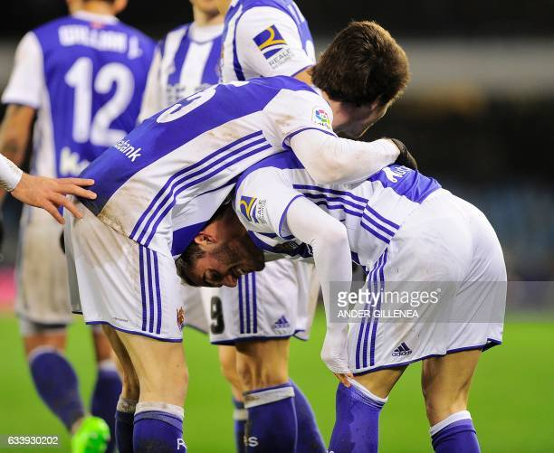 Real Sociedad's midfielder Juanmi is congratulated by teammate defender Aritz Elustondo after scoring his team's third goal during the Spanish league...