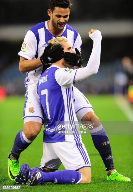 Real Sociedad's midfielder Juanmi is congratulated by teammate Brazilian forward Willian Jose after scoring his team's third goal during the Spanish...