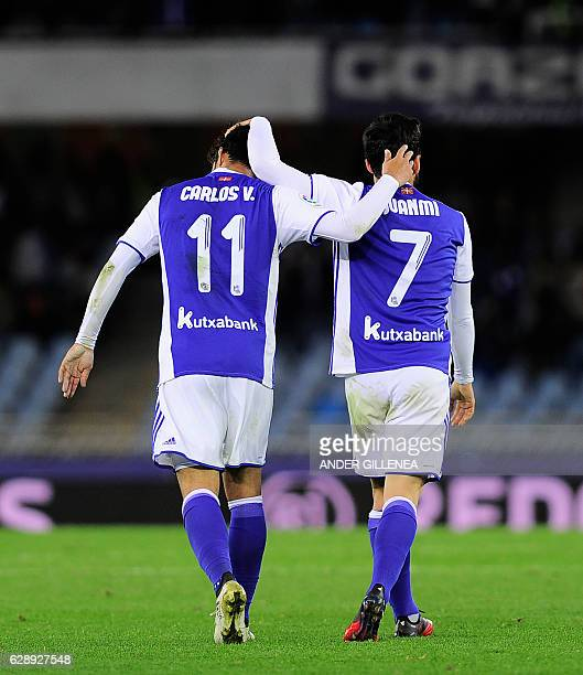 Real Sociedad's midfielder Juanmi is congratulated by teammate Mexican forward Carlos Vela after scoring his team's third goal during the Spanish...