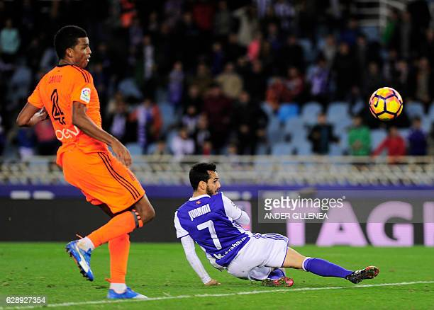 Real Sociedad's midfielder Juanmi shots to goal next to Valencia's Brazilian defender Aderlan Santos during the Spanish league football match Real...