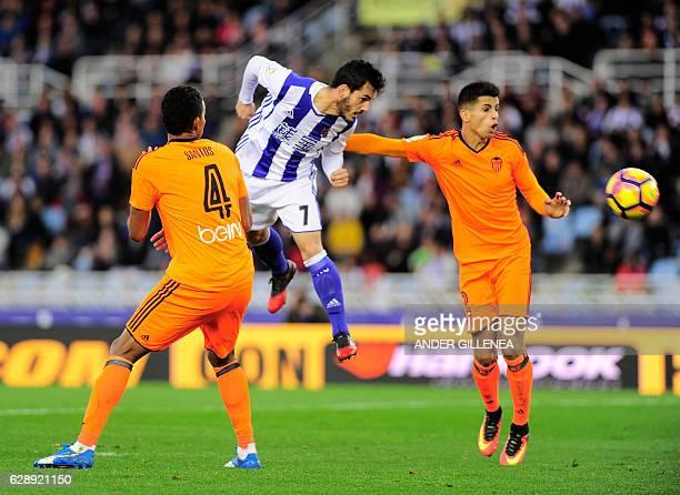 Real Sociedad's midfielder Juanmi vies with Valencia's Brazilian defender Aderlan Santos and Portuguese defender Joao Cancelo during the Spanish...