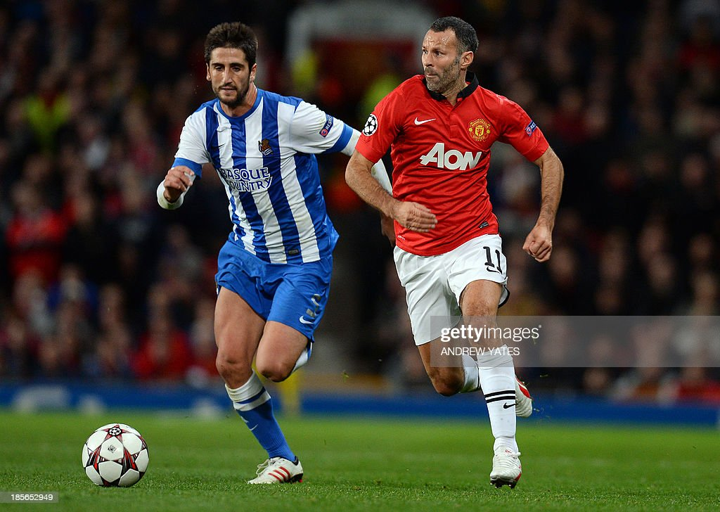 Real Sociedad's midfielder Markel Bergara (L) vies with Manchester United's Welsh midfielder Ryan Giggs during the UEFA Champions League football match between Manchester United and Real Sociedad at Old Trafford in Manchester, north west England on October 23, 2013.