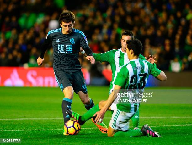 Real Sociedad's midfielder Mikel Oyarzabal vies with Betis' Algerian defender Aissa Mandi during the Spanish league football match Real Betis vs Real...