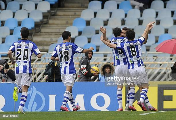 Real Sociedad's midfielder Xabi Prieto is congrtulated by teammates forward Imanol Agirretxe and midfielder Esteban Granero after scoring during the...