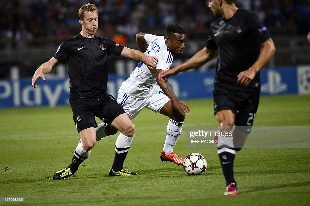 Real Sociedad's Spanish midfielder David Zurutuza (L) vies with Lyon's French forward Alexandre Lacazette (C) during the first leg of the UEFA Champions League's playoffs football match Olympique Lyonnais vs Real Sociedad on August 20, 2013 at the Gerland stadium in Lyon, eastern France.