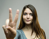 Portrait of young woman gesturing victory sign against gray background. Horizontal shot of real woman showing peace hand sign. Studio photography from a DSLR camera. Sharp focus on eyes.