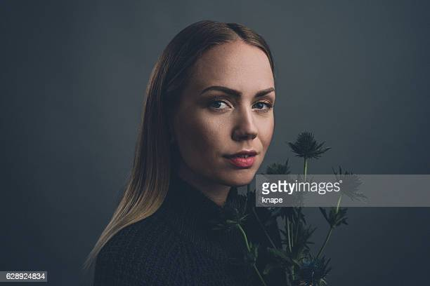 Real woman studio portrait holding thistle