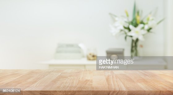 Real wood table top texture on white wall room background. : Stock Photo