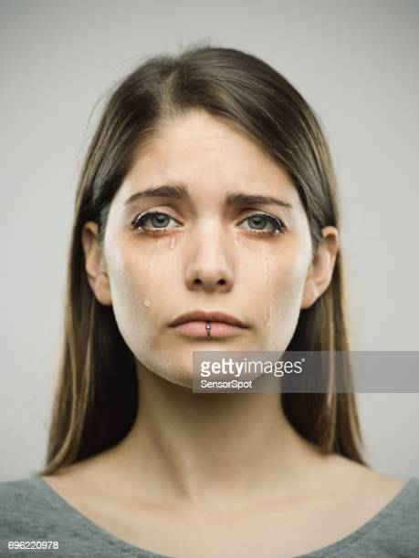 Real young woman crying studio portrait
